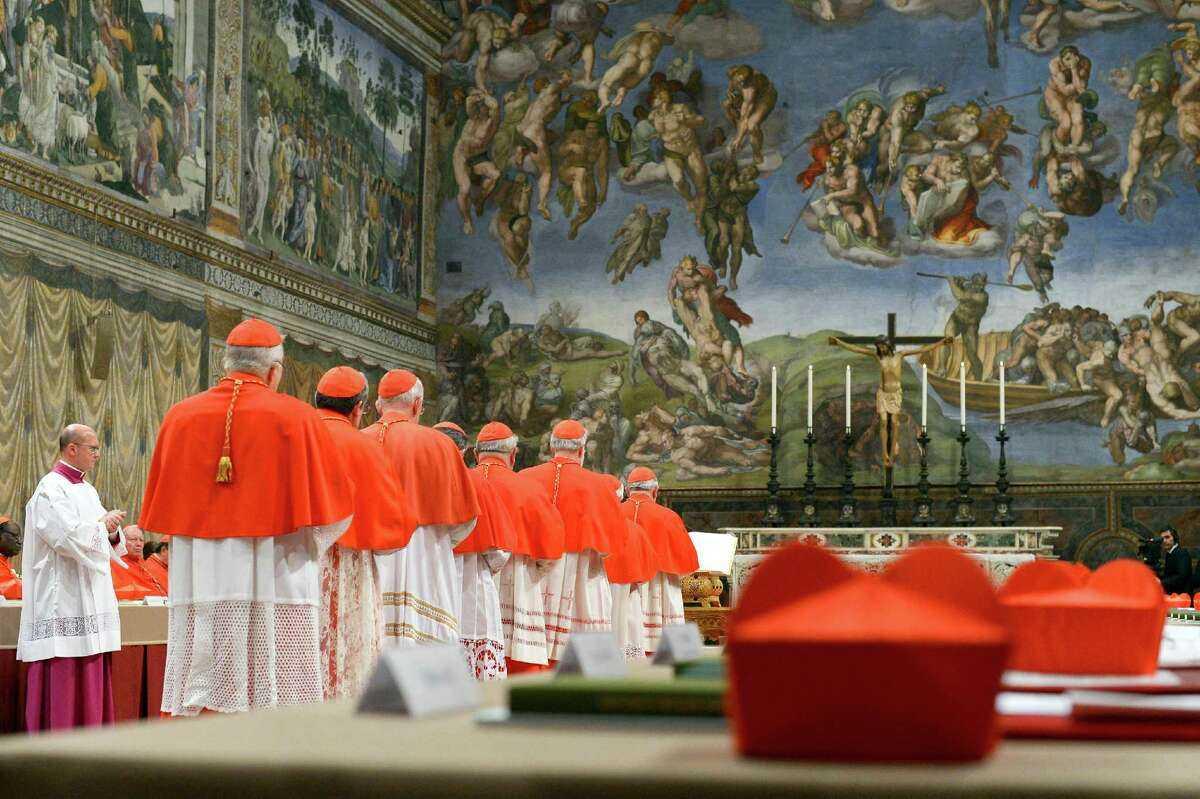 In this picture released by the Vatican newspaper L'Osservatore Romano, Cardinals line up to take an oath of secrecy inside the Sistine Chapel at the Vatican, Tuesday, March 12, 2013, before the start the conclave to elect the 266th Roman Catholic pope. Cardinals from around the globe locked themselves inside the Sistine Chapel on Tuesday to choose a new leader for the world's 1.2 billion Catholics and their troubled church, surrounded by Michelangelo's imposing frescos imagining the beginning and the end of the world. (AP Photo/L'Osservatore Romano, ho)