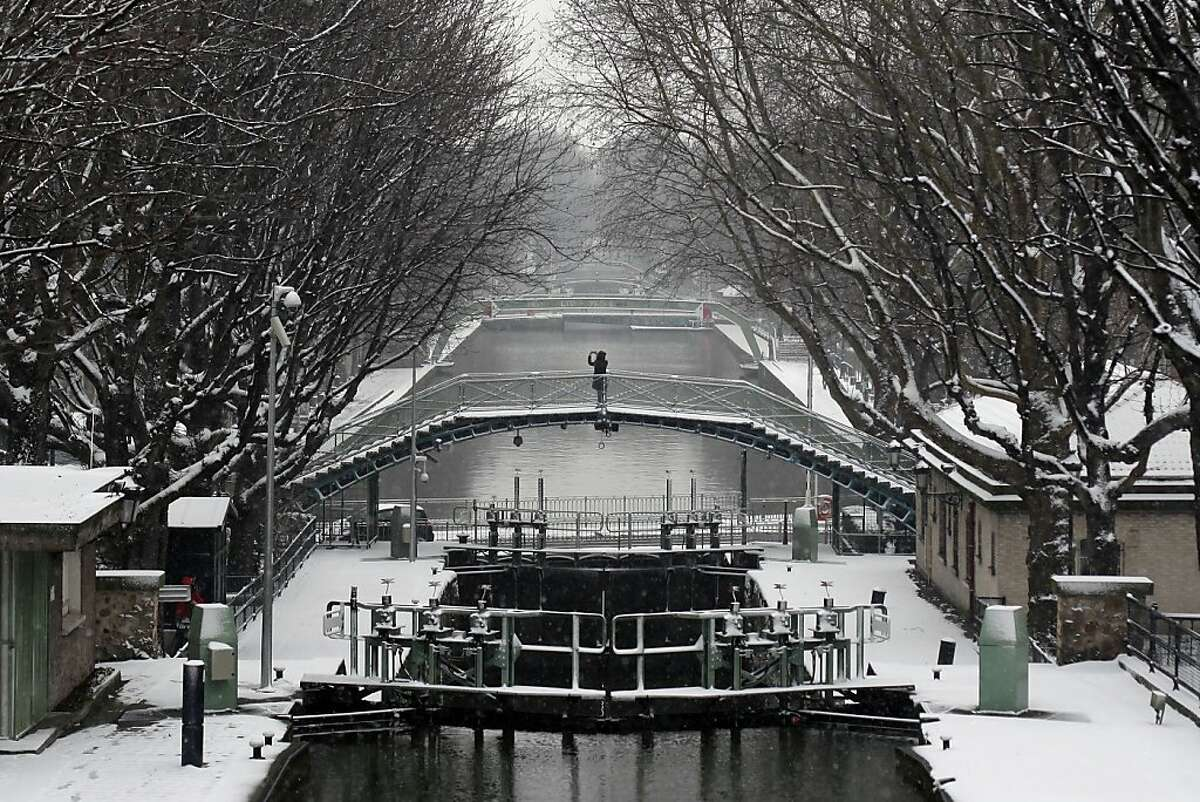 A pedestrian takes a photo from a bridge, at the canal St Martin, in Paris, Tuesday, March 12, 2013. Hundreds of flights out of Western Europe have been cancelled, no trains running under the English Channel, and Belgium's prince is stuck at home, all because of a sudden dump of oddly late snowfall on Western Europe. (AP Photo/Thibault Camus)