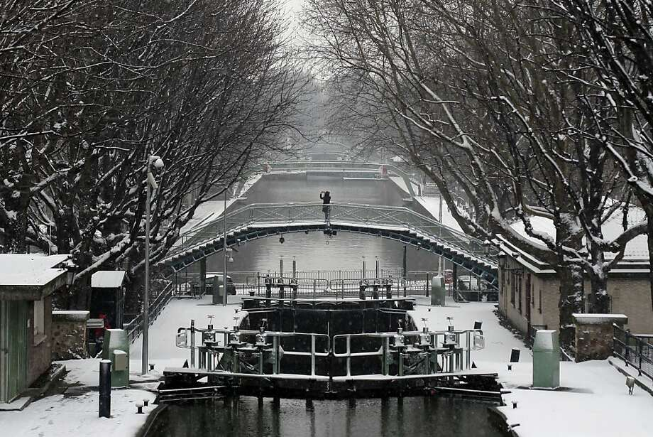 A pedestrian takes a photo from a bridge, at the canal St Martin, in Paris, Tuesday, March 12, 2013. Hundreds of flights out of Western Europe have been cancelled, no trains running under the English Channel, and Belgium's prince is stuck at home, all because of a sudden dump of oddly late snowfall on Western Europe.  Photo: Thibault Camus, Associated Press