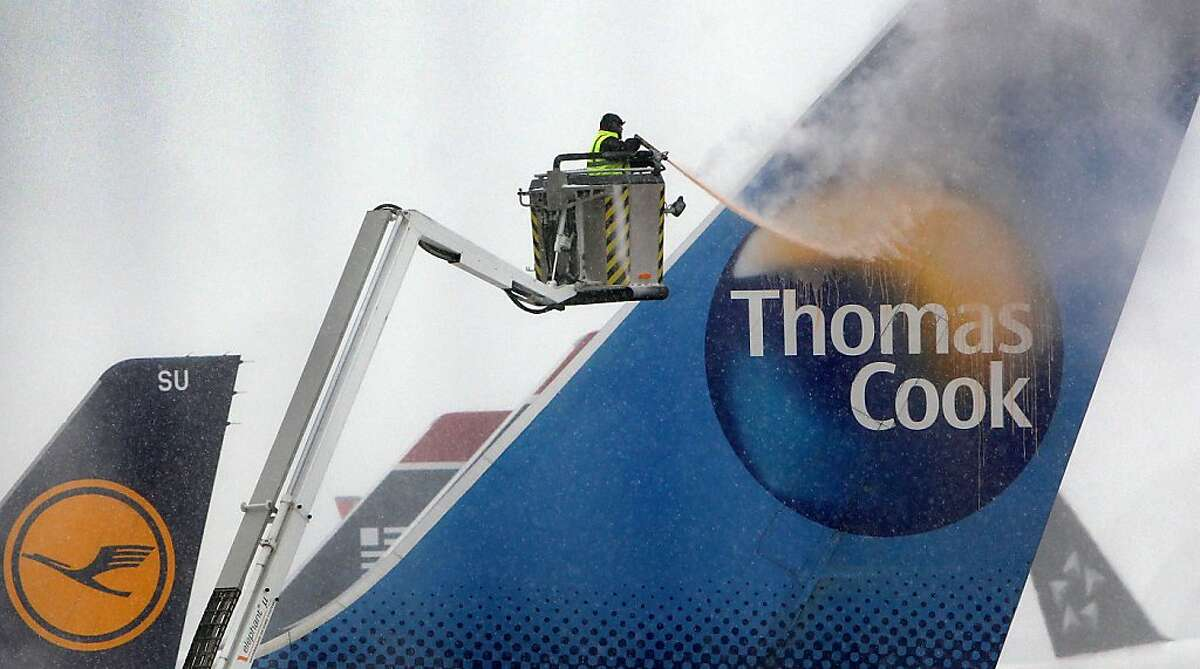 An airport employee uses a de-icing engine to defrost a Thomas Cook airplane on the snow covered ground of the airport in Frankfurt am Main, western Germany, on March 12, 2013 as the Europe's third-busiest hub was able to re-open one runway for takeoffs only on the afternoon, after being forced to close completely due to heavy snow.. AFP PHOTO / DANIEL ROLANDDANIEL ROLAND/AFP/Getty Images