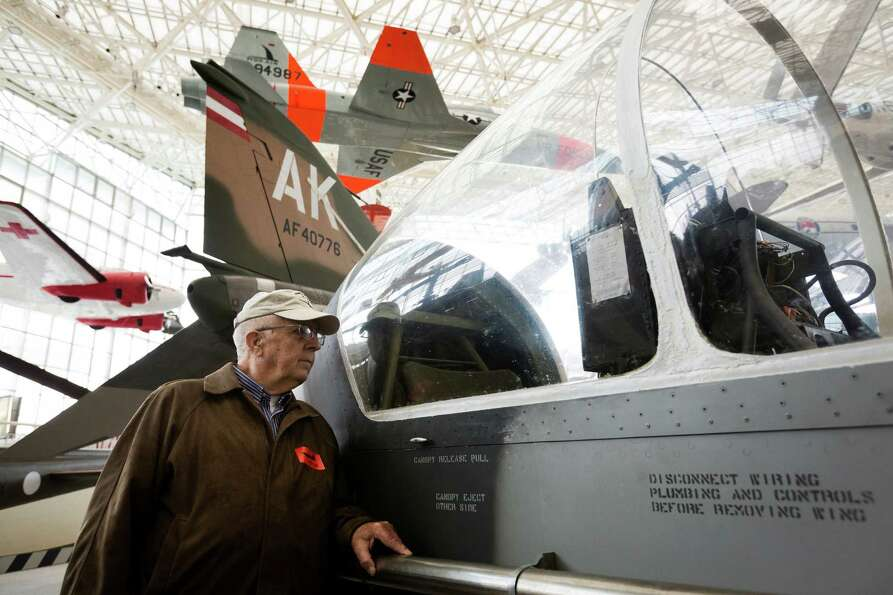 Retired Gen. George Walker leans against one of the freshly exhibited YO-3A spy planes he flew in th