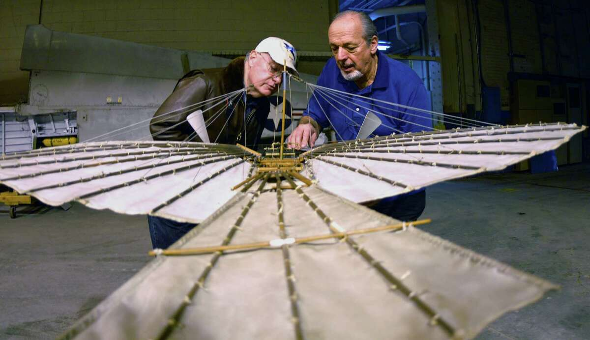 Connecticut Air and Space Center president Gene Madara and Andy Kosch, board of directors member work with a model of Gustave Whitehead's plane at the center in Stratford, Conn. on Tuesday March 12, 2013. The model was constructed by the late Bill Wargo. Kosch helped build and fly the replica, is the president of the project. For the 100th anniversary edition of Jane's All the World Aircraft, Whitehead's flyer will be given credit as the first operational heavier-than-air aircraft.