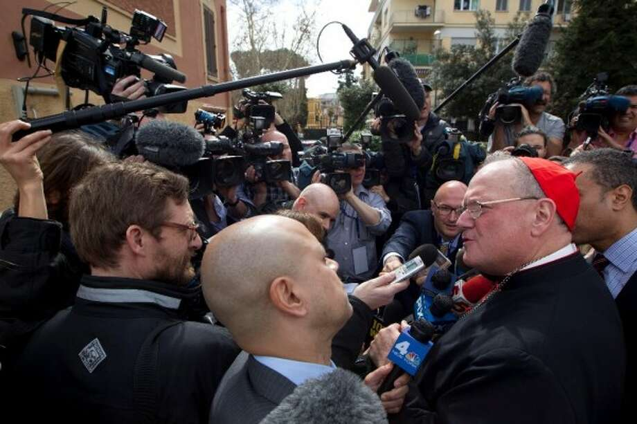 New York Archbishop Cardinal Timothy Dolan greets the media as he leaves the Saint Mary of Guadalupe church after celebrating mass, in Rome, Sunday March 10, 2013. (AP Photo/Andrew Medichini)