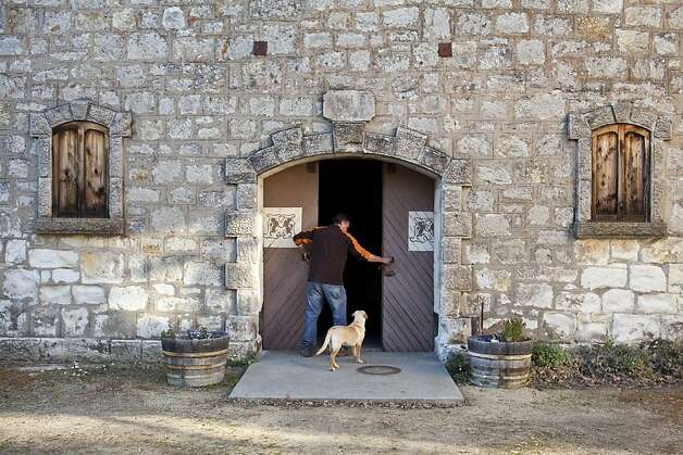 Chris Travers with Maya, his 4-month-old puppy, opens the Mayacamas stone cellar. Photo: Jason Henry, Special To The Chronicle