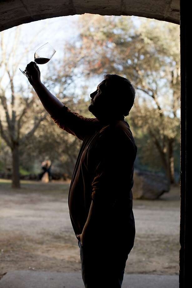 Chris Travers, part owner of Mayacamas Vineyards - whose stone winery was built in 1889 by John Henry Fisher atop 2,000-foot Mount Veeder - inspects a 1991 Cabernet Sauvignon. Photo: Jason Henry, Special To The Chronicle