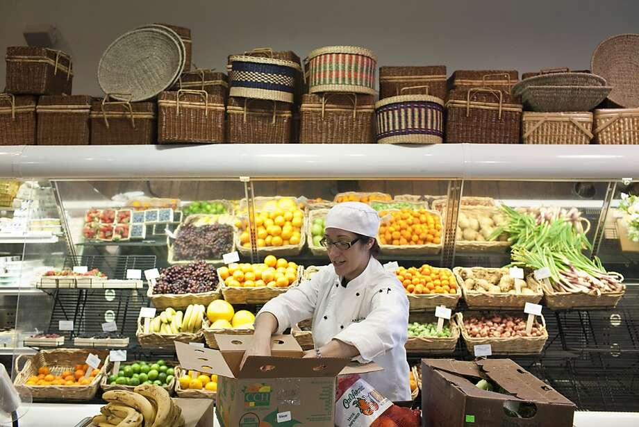 Lupita Fernandez stocks fruit at Dean & DeLuca in St. Helena. The gourmet grocery chain has stores in New York City, Washington and Charlotte, N.C. Photo: Jason Henry, Special To The Chronicle