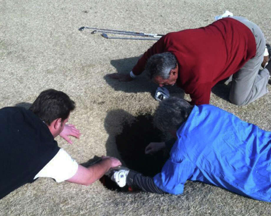 In this cell phone image taken March 8, 2013 and provided by golfmanna.com, Hank Martinez, top, Ed Magaletta, right, and Russ Nobbe, look into an 18-foot-deep and 10-foot- wide sinkhole that golfer Mark Minhal fell into while playing golf at the Annbriar Golf Course in Waterloo, Ill. Mihal, 43, a mortgage broker from Creve Coeur, Mo., was hoisted to safety with a rope and suffered a dislocated shoulder. (AP Photo/Courtesy of golfmanna.com, Mike Peters) Photo: Miker Peters