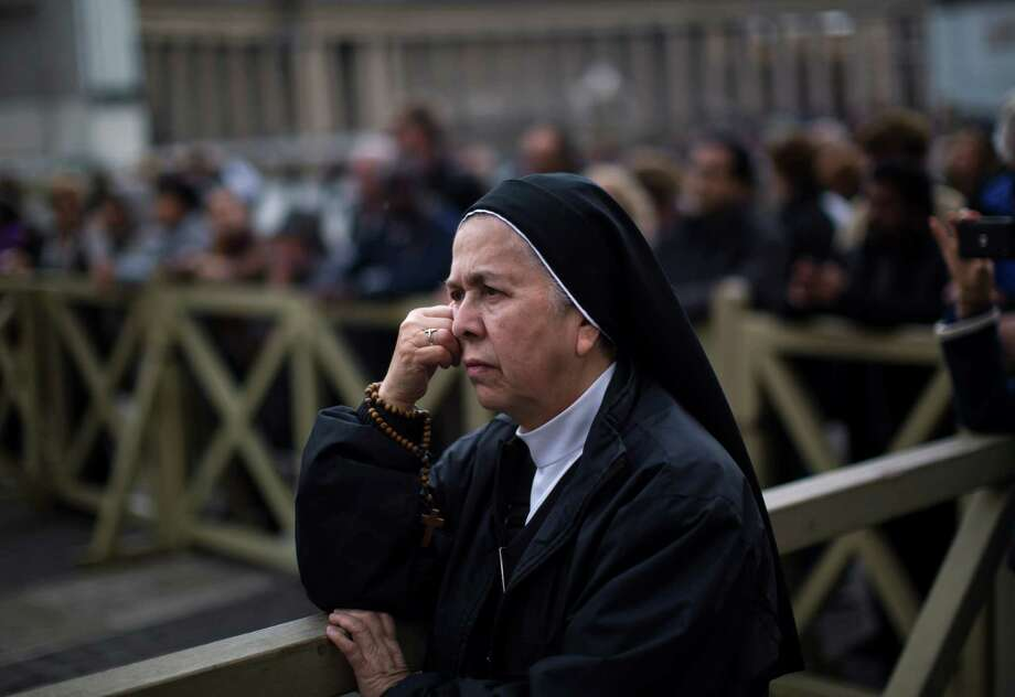 A nun follows a Mass taking place inside St.Peter's Basilica for the election of a new pope, broadcast on a giant screen, not pictured, in St. Peter's Square, at the Vatican, Tuesday, March 12, 2013. Cardinals enter the Sistine Chapel on Tuesday to elect the next pope amid more upheaval and uncertainty than the Catholic Church has seen in decades: There's no front-runner, no indication how long voting will last and no sense that a single man has what it takes to fix the many problems. Photo: Emilio Morenatti