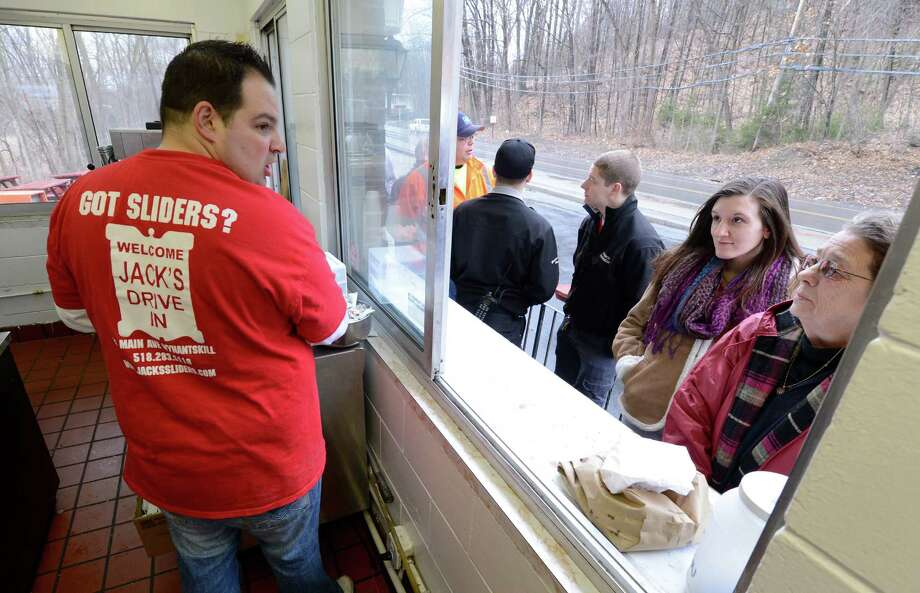 Al Deeb, left, takes orders from the faithful who have been standing in the rain on opening day of Jack's Drive In March 12, 2013 in Wynantskill, N.Y.  Jack's is know for their sauteed onion layered sliders and their opening is as much a rite of spring as the seeing the first robin in this area.     (Skip Dickstein/Times Union) Photo: SKIP DICKSTEIN / 10021521A