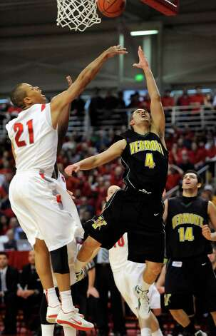 Vermont's Four McGlynn (4) shoots over Stony Brook's Al Rapier (21) during the second half of the  America East Conference tournament championship NCAA college basketball game on Saturday, March 10, 2012, in Stony Brook, NY. Vermont won 51-43. (AP Photo/Kathy Kmonicek) Photo: Kathy Kmonicek / FR170189 AP