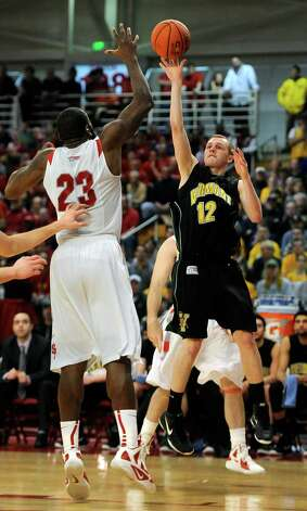 Vermont's Sandro Carissimo (12) shoots over Stony Brook's Dallis Joyner (23) during the second half of the  America East Conference tournament championship NCAA college basketball game on Saturday, March 10, 2012, in Stony Brook, NY. Vermont won 51-43. (AP Photo/Kathy Kmonicek) Photo: Kathy Kmonicek / FR170189 AP