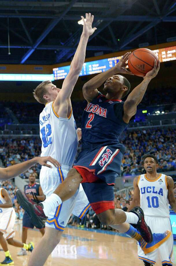 Arizona guard Mark Lyons, right, goes up for a shot as UCLA forward David Wear defends during the second half of an NCAA college basketball game, Saturday, March 2, 2013, in Los Angeles. UCLA won 74-69. (AP Photo/Mark J. Terrill) Photo: Mark J. Terrill / AP