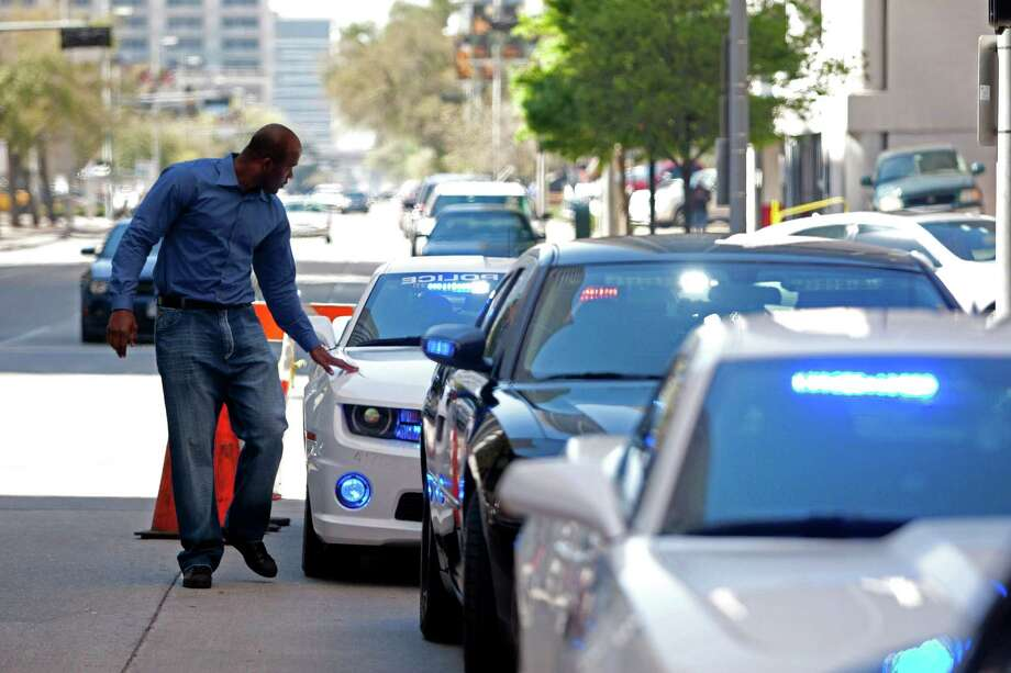 Former Houston Texans defensive lineman Mario Williams touches one of the five specially equipped 2013 Dodge Chargers he donated to HPD's Traffic Enforcement Division at police headquarters downtown, Tuesday, March 12, 2013, in Houston. Photo: Johnny Hanson, Houston Chronicle / © 2013  Houston Chronicle