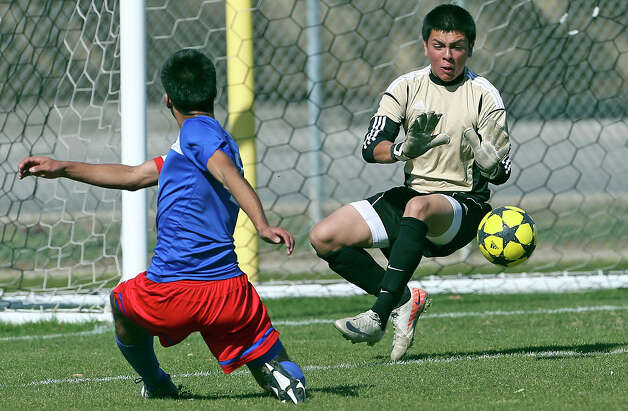 Jefferson's Marco Cruz slips the ball by Fernando Delgado for the game's only score as Jefferson beats Edison 1-0 in soccer at the SAISD Spring Sports Complex on March 12, 2013. Photo: Tom Reel, San Antonio Express-News