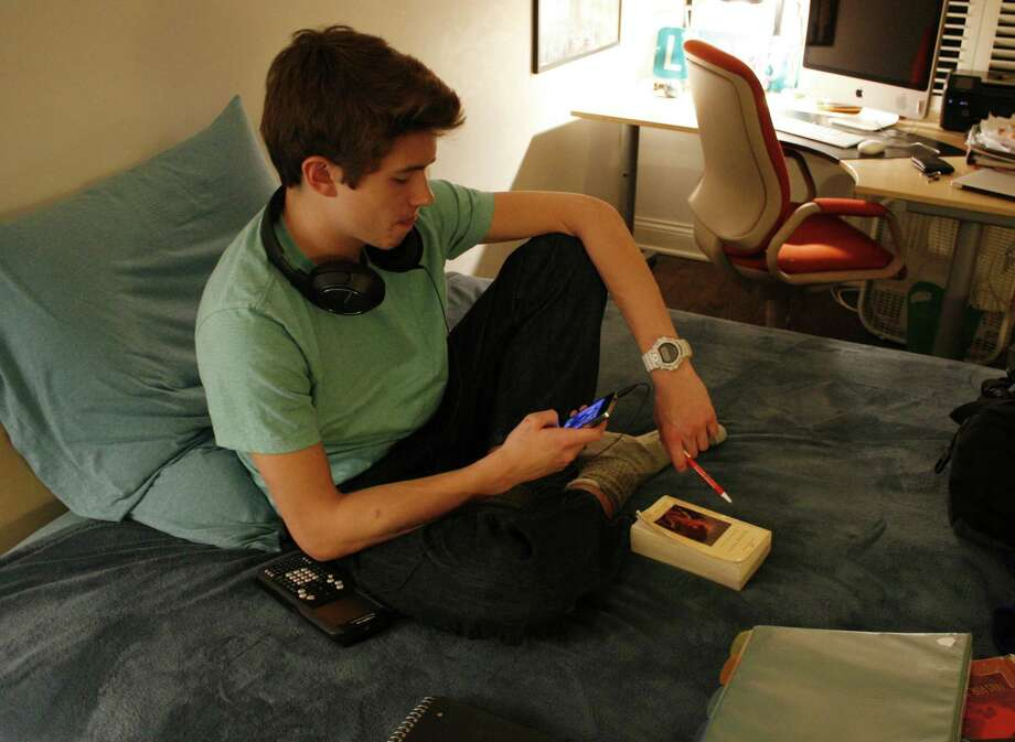 HOLD FOR RELEASE UNTIL 12:01 A.M. EDT. THIS STORY MAY NOT BE PUBLISHED, BROADCAST OR POSTED ONLINE BEFORE 12:01 A.M. EDT - Donald Conkey, 15, checks his smartphone while doing homework in his bedroom on Monday, March 11, 2013, in Wilmette, Ill. A new report from the Pew Internet & American Life Project says more teens are using smartphones as a main means of accessing the Internet -- moreso than adults. (AP Photo/Martha Irvine) Photo: Martha Irvine