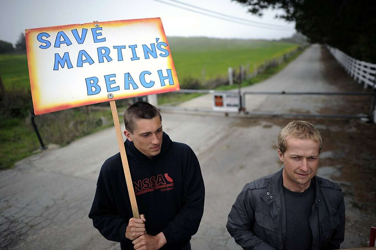 (L-R) Surfers Konrad Wallace and Dylan Christensen, hold signs as they protest the closure of the gate on the now private road leading to Martin's Beach in Half Moon Bay Tuesday March 12th, 2013.