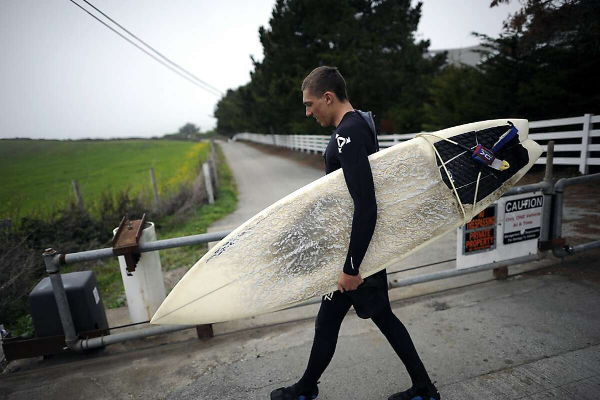 Surfer Konrad Wallace of El Granada walks past the gate on the now private road on his way to Martin's Beach in Half Moon Bay Tuesday March 12th, 2013.