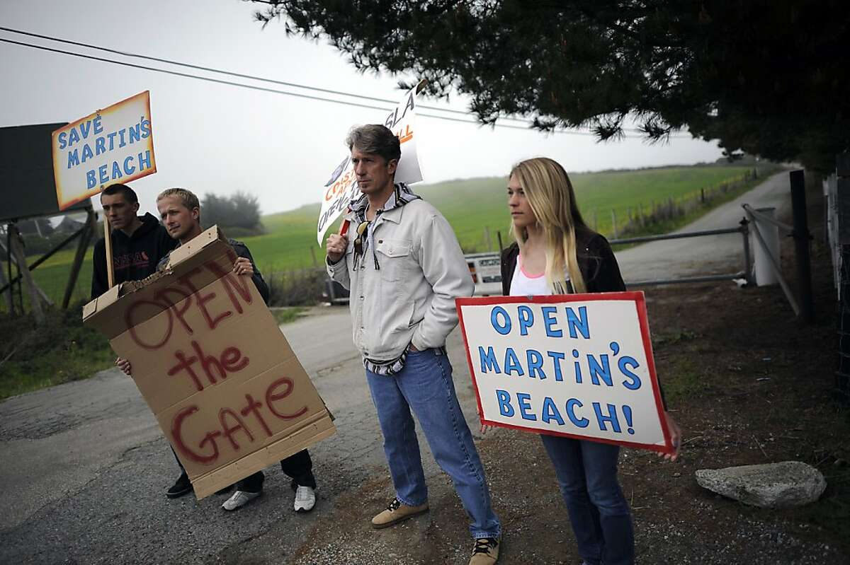 (L-R) Surfers Konrad Wallace, Dylan Christensen, Mike Wallace and Kaira Wallace hold signs as they protest the closure of the gate on the now private road leading to Martin's Beach in Half Moon Bay Tuesday March 12th, 2013.