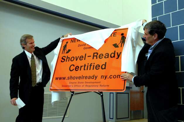 Ed Abele, left, and his brother Chris Abele, right, both of Abele Builders, unveil a sign announcing the status of Global Business Park-North during a news conference in March 2010 at the Halfmoon Town Hall. (Cindy Schultz / Times Union) Photo: CINDY SCHULTZ / 00007983A