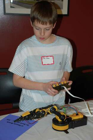 "Lucas Quinn, 12, built a robotic arm which he displayed at New Canaan's Tech Night Feb. 26. ""I've always thought it was cool having a robotic arm,"" he said, excited by the work he does with the Tech Team at Saxe Middle School. Photo by Jarret Liotta Photo: Contributed Photo"