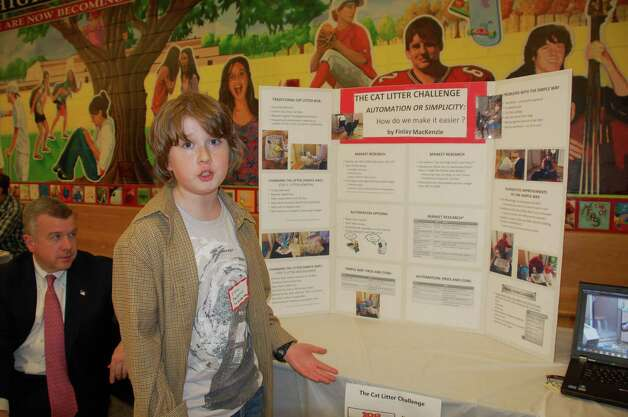 "Finlay MacKenzie, 11, discovered that ""There is no shortcut to cleaning up after your cat."" MacKenzie presented his experiment at New Canaan's Tech Night Feb. 26. His father, Clark MacKenzie, left, took part in the experiment by doing the dirty work. Photo by Jarret Liotta Photo: Contributed Photo"