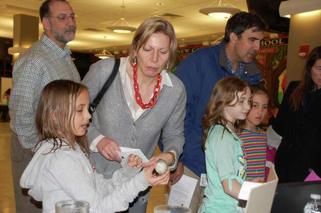 "Lucy Potter, 10, explains the ""Eggsperiment,"" which demonstrates how certain liquids affect one's teeth, to parent Gertraud Humphreys, at New Canaan Public School's Tech Night Feb. 26. ""I think it's a great opportunity for the kids to showcase what they learned and they seem energized by it,"" Humphreys said. Photo: Contributed Photo"