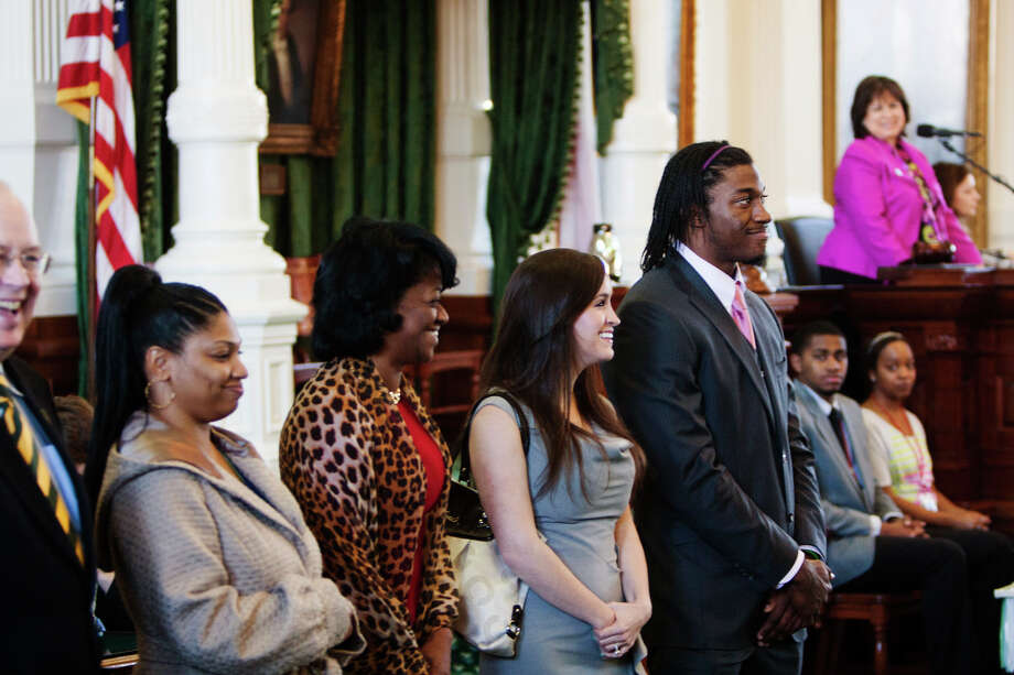 In this photo provided by Texas Senate Media Services, Washington Redskins' Robert Griffin III, right, appears before both chambers of the Texas Legislature for resolutions honoring his football career, Tuesday, March 12, 2013, in Austin, Texas. Attending to the left of Griffin at the Texas Capitol is his fiance Rebecca Liddicoat. Photo: Associated Press / Texas Senate Media Services