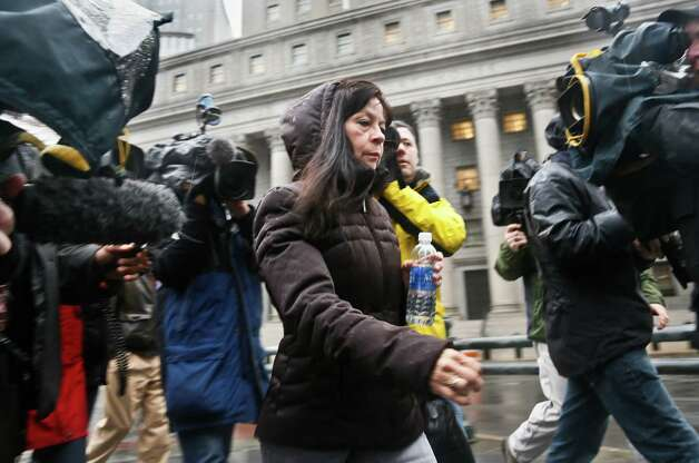 "Elizabeth Valle is surrounded by news reporters as she leaves court on Tuesday, March 12, 2013 in New York.   A federal jury convicted her son, New York City police officer Gilberto Valle, of charges he plotted to kidnap and cook women to dine on their ""girl meat.""   Valle, 28,  faces up to life in prison when he is sentenced on June 19. With the conviction, he loses his job as a police officer.  (AP Photo/Bebeto Matthews) Photo: Bebeto Matthews"