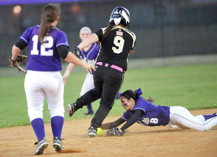 Lady Bulldog #9, Taylor Davis, skirts the ball as she scrambles safely back to second base, despite the efforts of Lady Indian #8, Ricki Gilbert. The Port Neches-Groves girls softball team hosted the Nederland High School girls team Tuesday Tuesday night in a 20-4A District game.    The Indians wone the game 7-3.   Dave Ryan/The Enterprise Photo: Dave Ryan