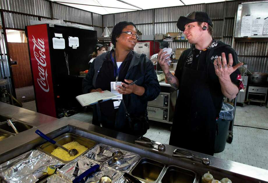 Houston health inspector Marcia Washington takes notes as she talks with Freebirds World Burrito kitchen manager Dominick Dambrosio. Photo: Cody Duty, Staff / © 2013 Houston Chronicle