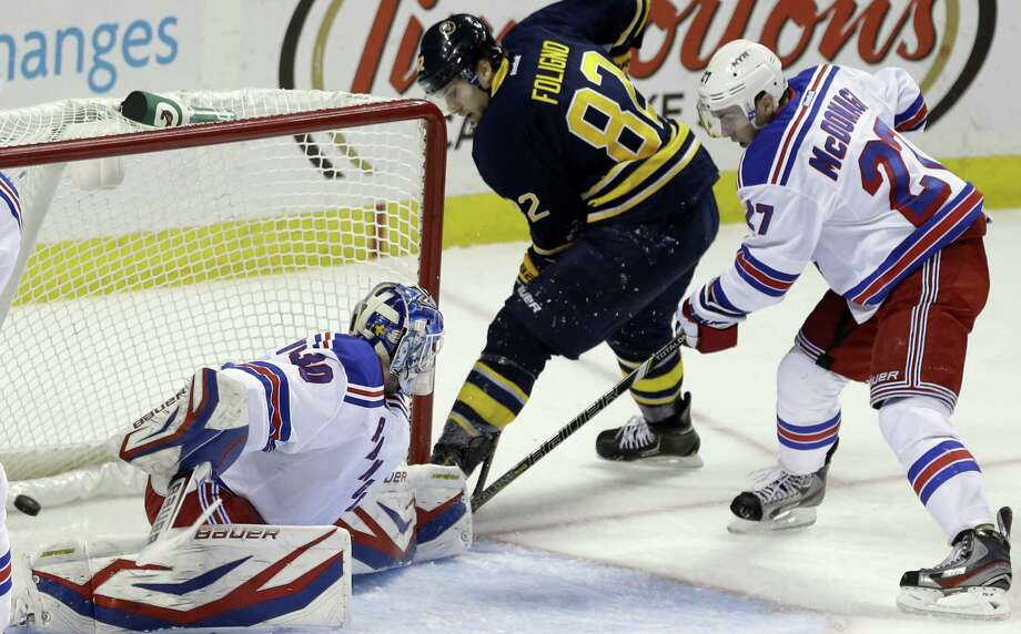 Buffalo Sabres' Marcus Foligno (82) scores on New York Rangers' Henrik Lundqvist of Sweden as Rangers' Ryan McDonagh (27) defends during the second period of an NHL hockey game in Buffalo, N.Y., Tuesday, March 12, 2013. (AP Photo/David Duprey) Photo: David Duprey