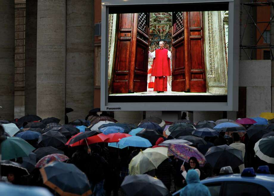 """People watch on a video monitor in St. Peter's Square as Monsignor Guido Marini, master of liturgical ceremonies, closes the double doors to the Sistine Chapel after shouting """"Extra omnes,"""" Latin for """"all out,"""" telling everyone but those taking part in the conclave to leave the frescoed hall. He then locked it at the Vatican, Tuesday, March 12, 2013. (AP Photo/Michael Sohn) Photo: Michael Sohn"""