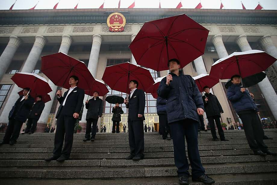 Soldiers dressed as ushers hold umbrellas in the rain at the entrance of the Great Hall of the People as they wait for delegates arrive to the closing session of the annual Chinese People's Political Consultative Conference (CPPCC) on March 12, 2013 in Beijing, China. The newly-elected Chairman of the CPPCC Yu Zhengsheng pledged Tuesday that China will not copy Western political systems under any circumstances.  Photo: Feng Li, Getty Images