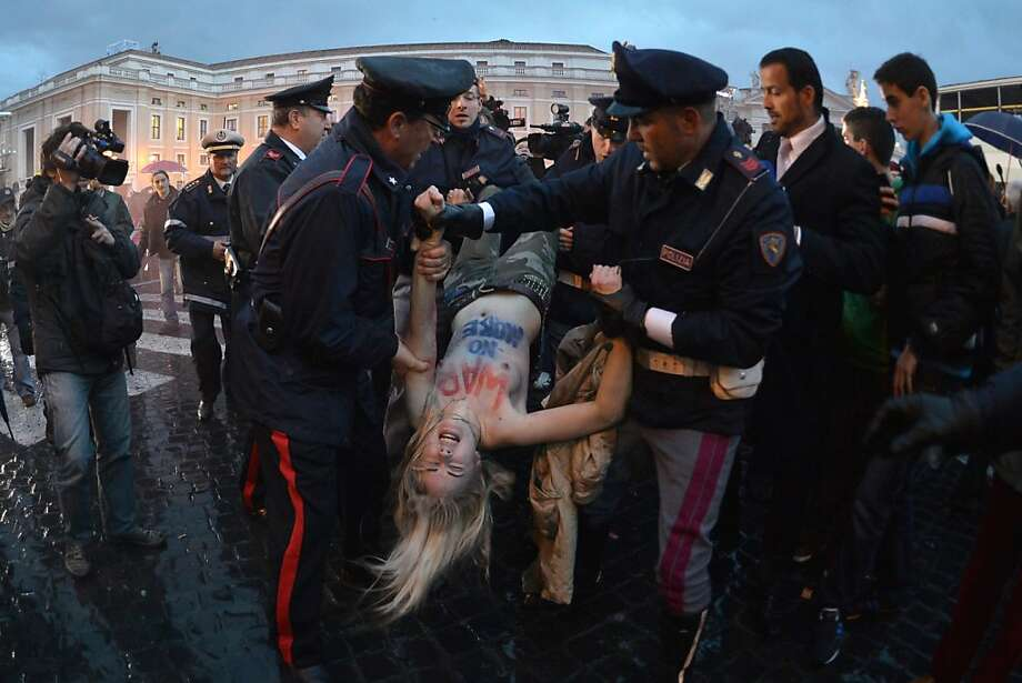 An activist from the feminist group Femen is taken away by policemen during a protest a few meters from St Peter's square during a papal election conclave on March 12, 2013 near the Vatican.  Cardinals prepared Tuesday for the start of an historic conclave to elect a new pope after Benedict XVI's shock resignation, with the odds favoring a Western conservative to lead the Catholic world.  Photo: Gabriel Bouys, AFP/Getty Images