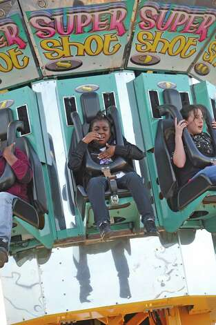 Key'aira Overstreet, center, rides the Super Shot, a ride that goes straight up to the top of itself and then drops riders straight back down. The annual Nederland Heritage Festival kicked off Tuesday afternoon in downtown Nederland.  It will run through the rest of the week. Dave Ryan/The Enterprise Photo: Dave Ryan