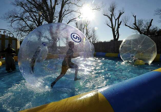 "Running around in a giant bubble in a big tank of water is Brice Perrman, 14, of Nederland.  One spectator described the ride as a giant ""Hamster Ball"" ride in water.   The annual Nederland Heritage Festival kicked off Tuesday afternoon in downtown Nederland.  It will run through the rest of the week. Dave Ryan/The Enterprise Photo: Dave Ryan"