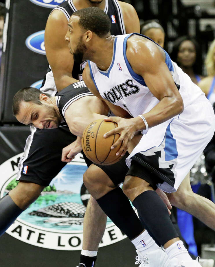 San Antonio Spurs' Manu Ginobili of Argentina, left, tries to get the ball away from Minnesota Timberwolves' Derrick Williams in the first half of an NBA basketball game Tuesday, March 12, 2013, in Minneapolis. Photo: Jim Mone, Associated Press / AP