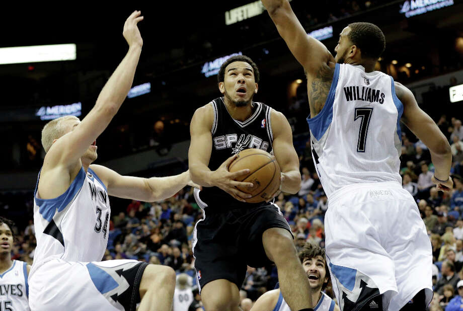 San Antonio Spurs' Cory Joseph, center, splits Minnesota Timberwolves defenders Greg Stiemsma, left, and Derrick Williams as he lays up in the first half of an NBA basketball game Tuesday, March 12, 2013, in Minneapolis. Photo: Jim Mone, Associated Press / AP