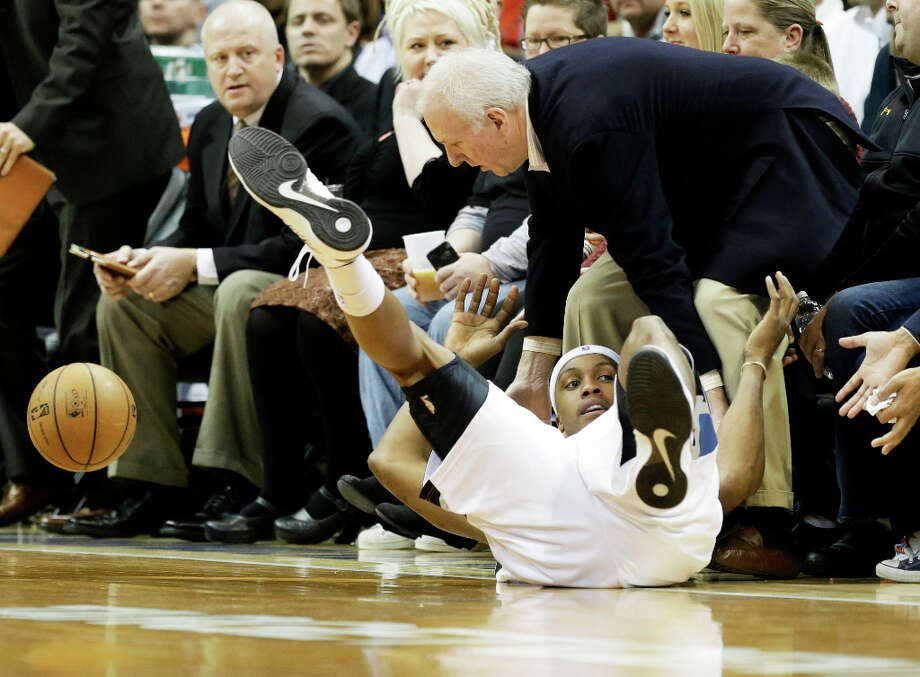 San Antonio Spurs head coach Gregg Popovich, right, comes to the aid of Minnesota Timberwolves' Dante Cunningham  as he goes out of bounds for the loose ball n the first half of an NBA basketball game Tuesday, March 12, 2013, in Minneapolis. Photo: Jim Mone, Associated Press / AP
