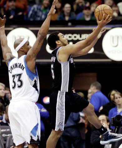 San Antonio Spurs' Cory Joseph, right, lays up a shot as Minnesota Timberwolves' Dante Cunningham  defends in the second half of an NBA basketball game Tuesday, March 12, 2013, in Minneapolis. The Timberwolves won 107-83. Joseph led the Spurs with 15 points. Photo: Jim Mone, Associated Press / AP