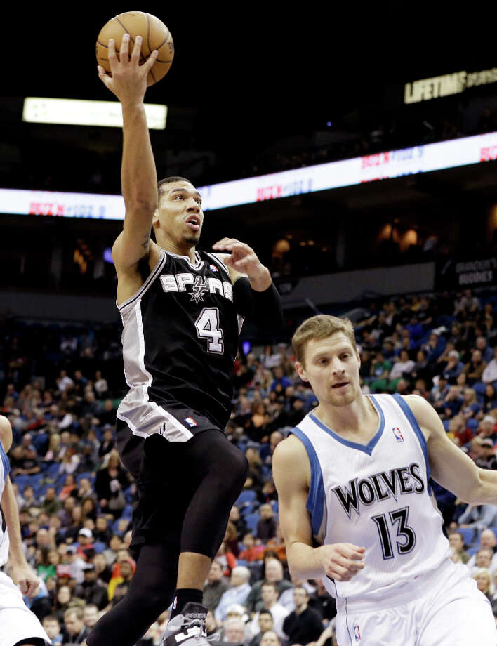 San Antonio Spurs' Danny Green, left, lays up behind Minnesota Timberwolves'  Luke Ridnour in the first half of an NBA basketball game Tuesday, March 12, 2013, in Minneapolis. Photo: Jim Mone, Associated Press / AP