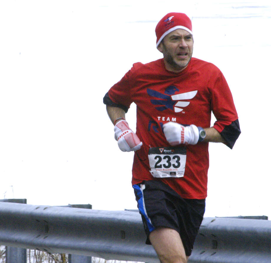 Against the backdrop of the ice-covered lake, veteran Mark LoSacco, 44, of New Milford settles in for the long haul on his way to an eight-place finish in the 29th edition of the Polar Bear Run road race around Lake Waramaug, March 3, 2013 Photo: Norm Cummings