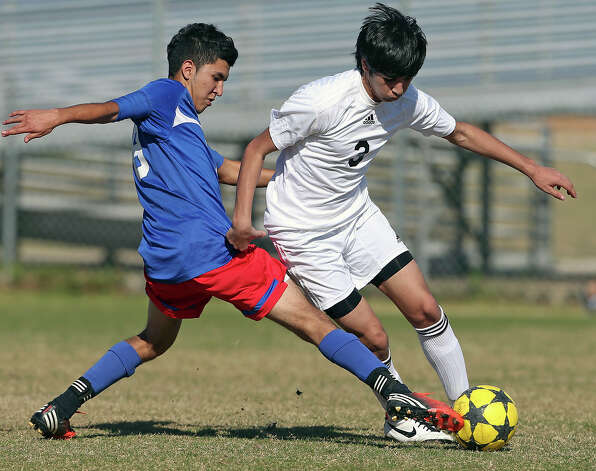 Mustang defender Ismael Rodriguez reaches in to tackle Daniel Jaramillo as Jefferson beats Edison 1-0 in soccer at the SAISD Spring Sports Complex on March 12, 2013. Photo: Tom Reel, San Antonio Express-News