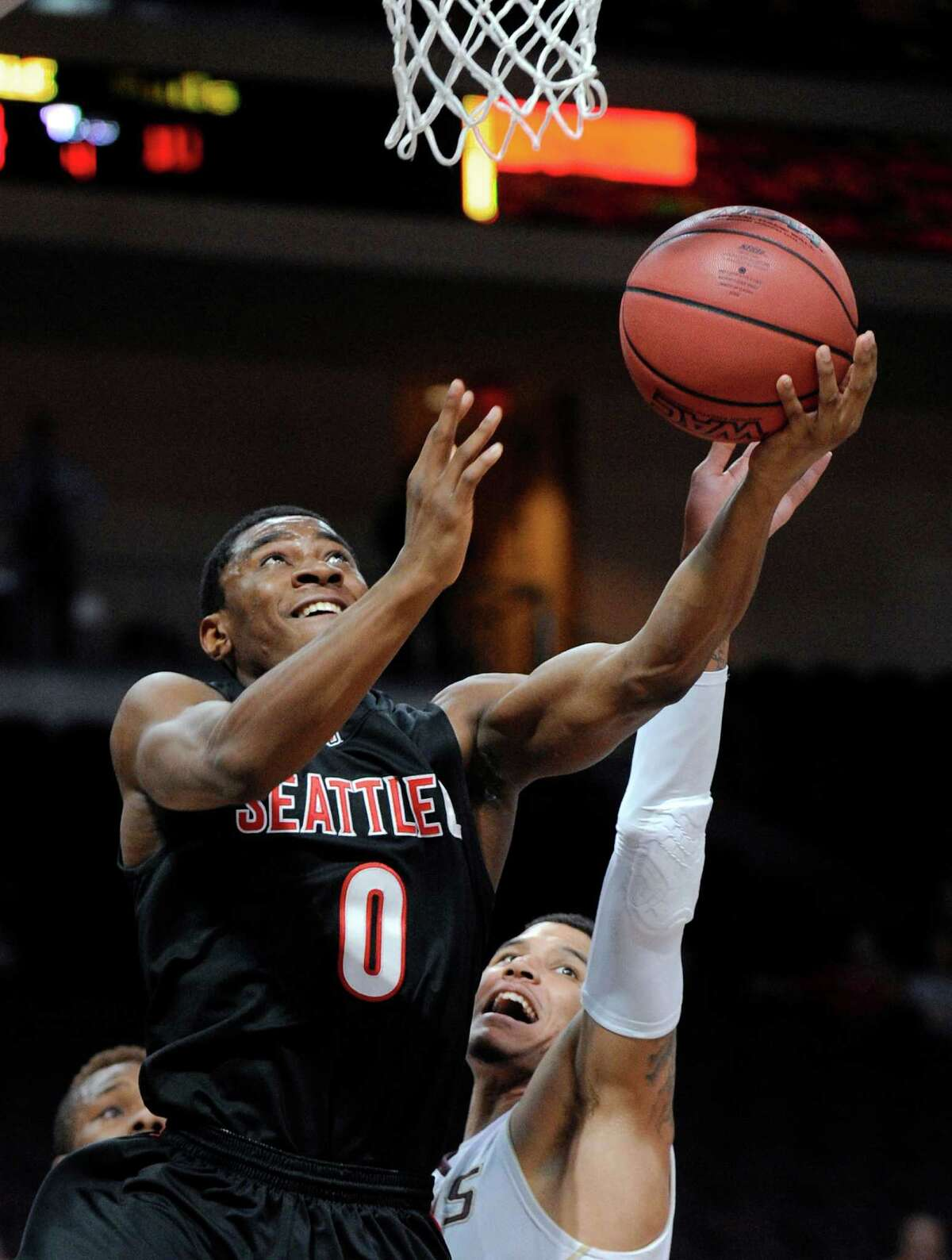 Seattle's Prince Obasi (0) shoot as Texas State's Corey Stern (5) defends during the first half of a Western Athletic Conference tournament NCAA college basketball game, Tuesday, March 12, 2013, in Las Vegas. (AP Photo/David Becker)