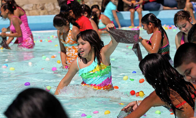 Britney Villalobos scrambles for Easter eggs after Councilman Chris Medina pronounces the opening of Woodlawn pool for Spring Break on March 12, 2013. Photo: TOM REEL