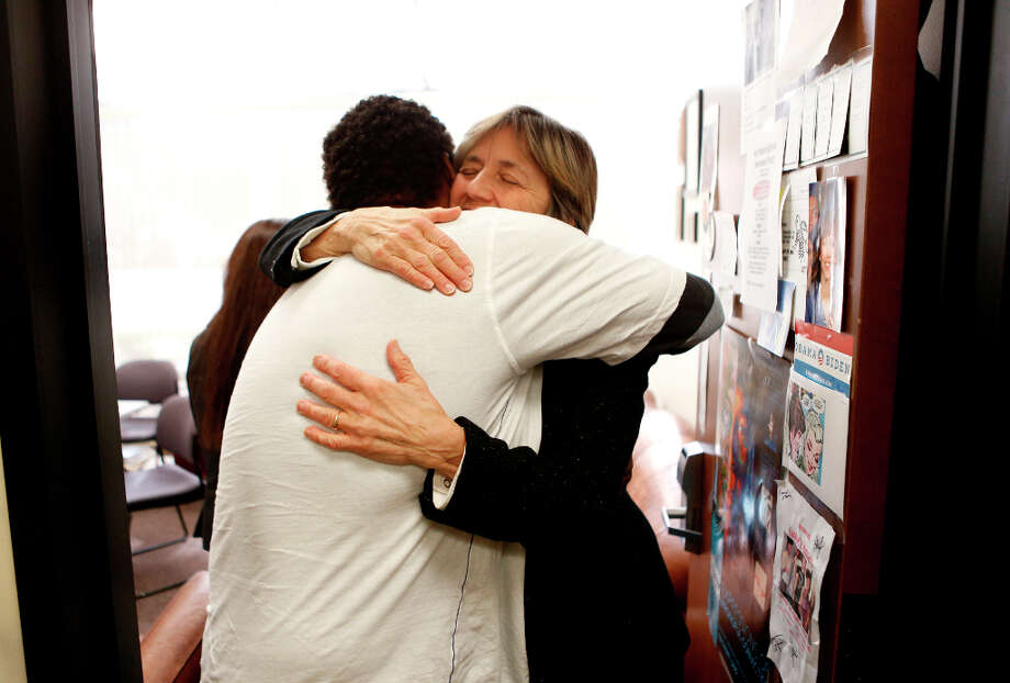 Johnny Williams (left), of East Oakland, hugs Innocence Project executive director Kathleen Ridolfi at the Innocence Project offices on Tuesday, March 12, 2013 in Santa Clara, Calif. I'm a hugger, Williams told Ridolfi. Photo: Beck Diefenbach, Special To The Chronicle / ONLINE_YES