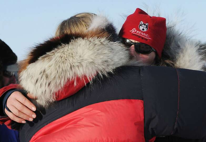 Aliy Zirkel, right, gets a hug before leaving White Mountain, Alaska, Tuesday, March 12, 2013, durin