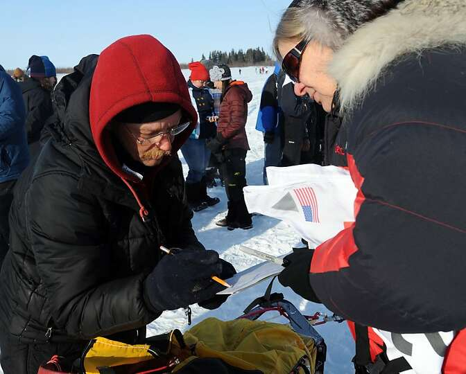 Mitch Seavey signs out of the White Mountain checkpoint in Alaska, Tuesday, March 12, 2013, during t