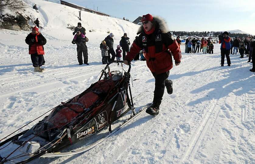 Aliy Zirkle runs next to her sled as she leaves White Mountain in Alaska, Tuesday, March 12, 2013, d