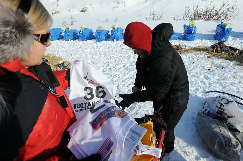 Volunteer Beverly Andersson, left, hands Mitch Seavey his race bib at White Mountain in Alaska, Tues